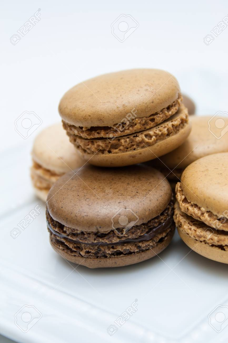 Vanilla, coffee and chocolate flavor french macaroons on a white plate Stock Photo - 12674980