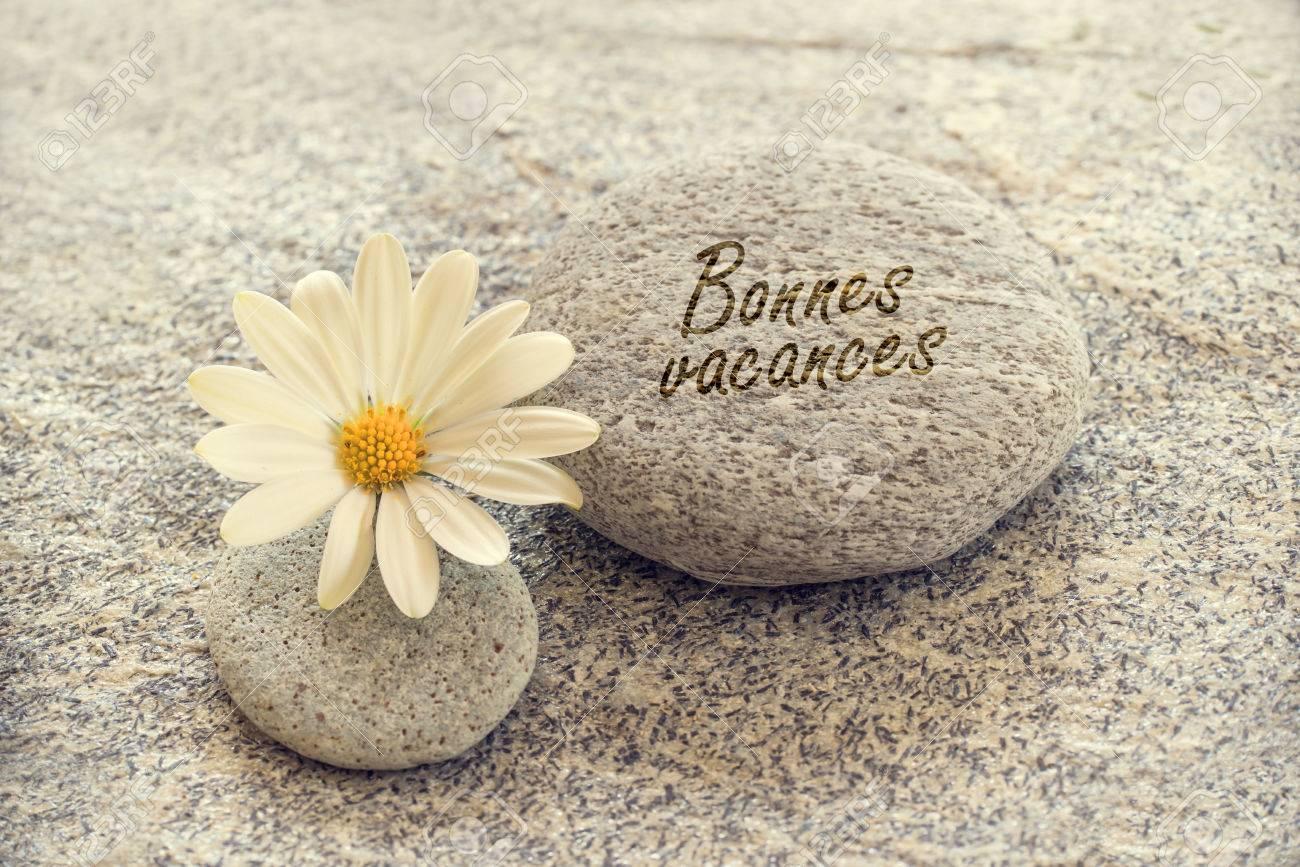 Bonnes vacances meaning happy holiday written on zen pebbles bonnes vacances meaning happy holiday written on zen pebbles with a daisy stock photo izmirmasajfo
