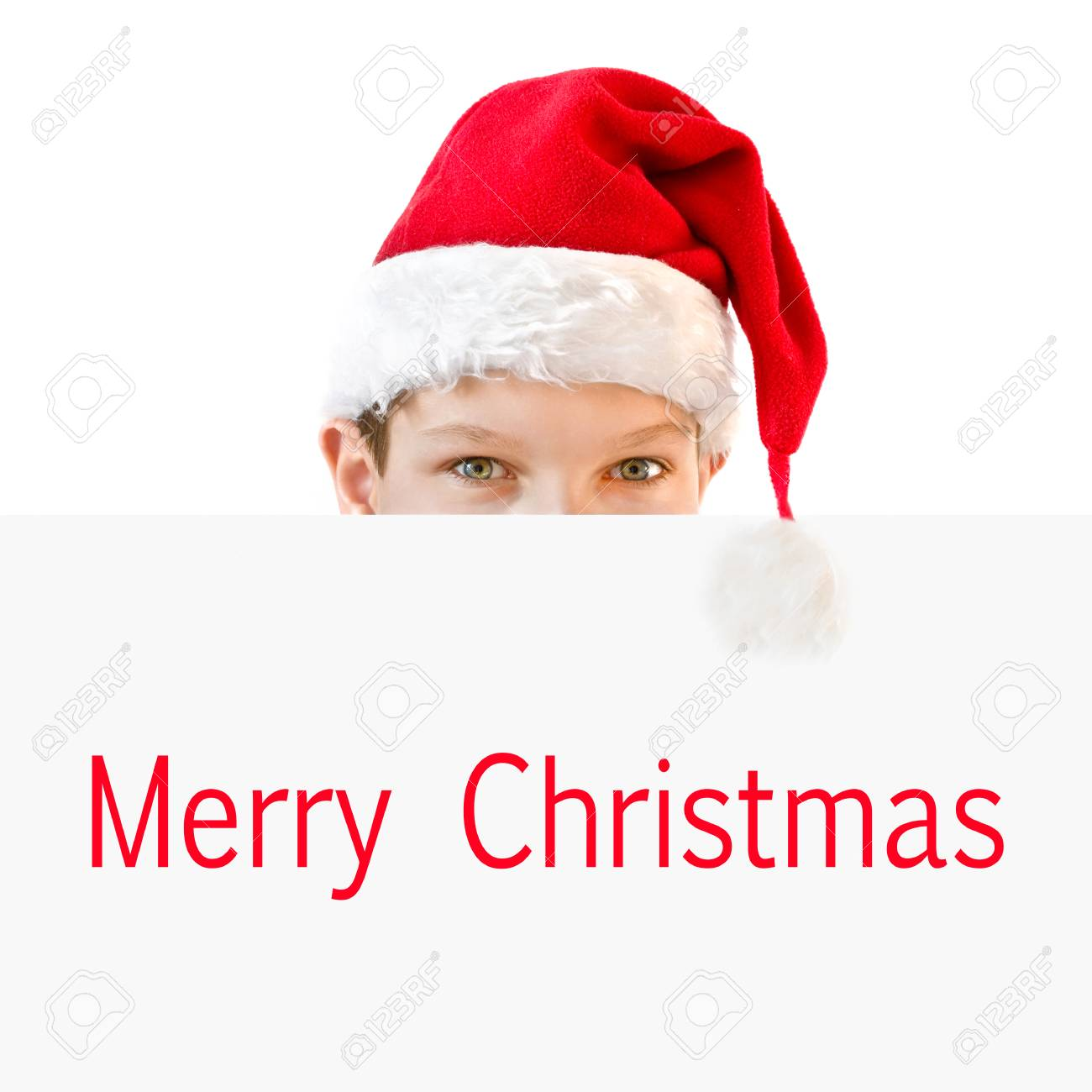 young boy in red santa hat hiding behind a paper merry christmas
