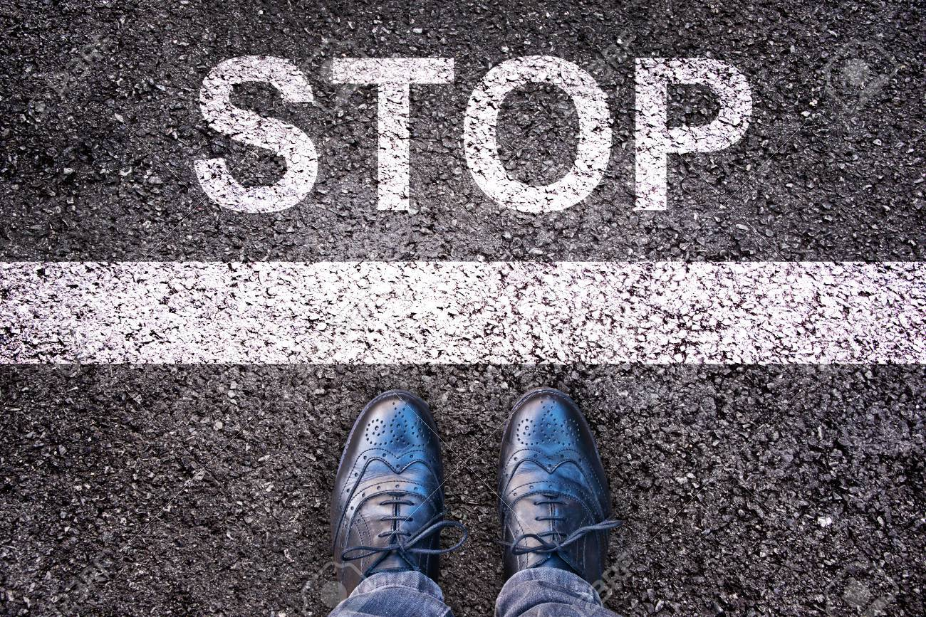 Word Stop written on an asphalt road with legs and shoes - 51573685