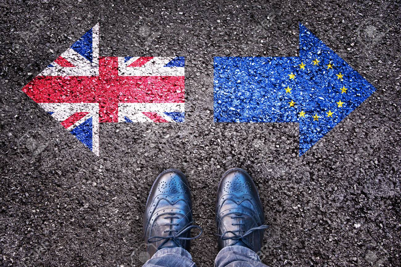 Brexit, flags of the United Kingdom and the European Union on asphalt road with legs - 61288385