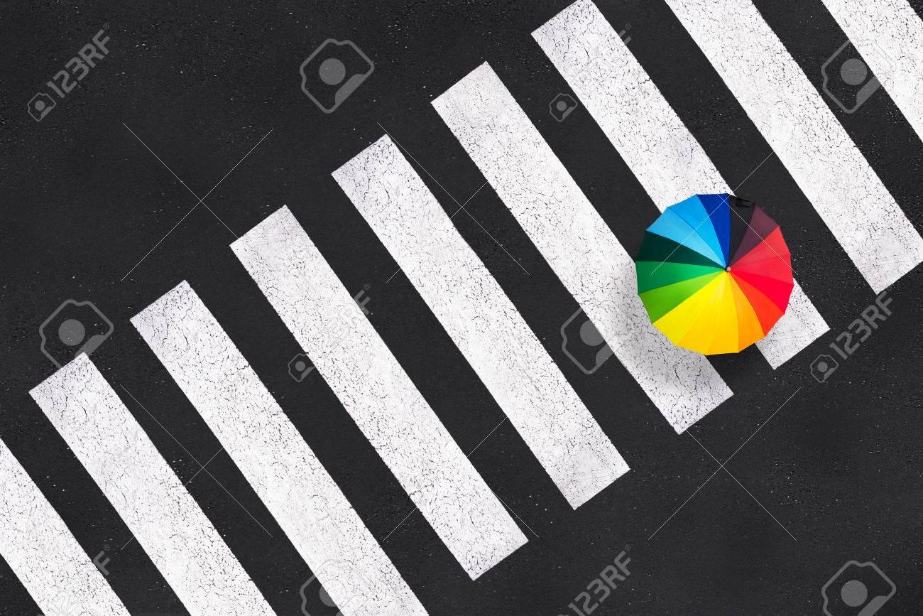 Top view of a rainbow umbrella on a pedestrian crosswalk - 63621034
