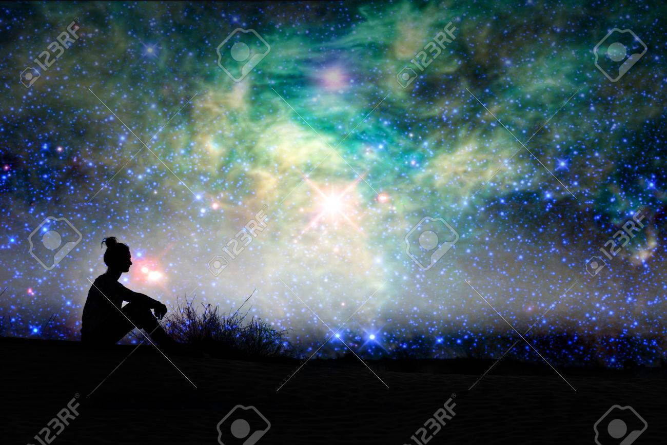 Silhouette of a woman sitting outside, starry night background - 68115620