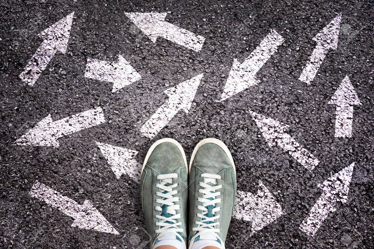 Sneaker shoes and arrows pointing in different directions on asphalt ground, choice concept - 119776553