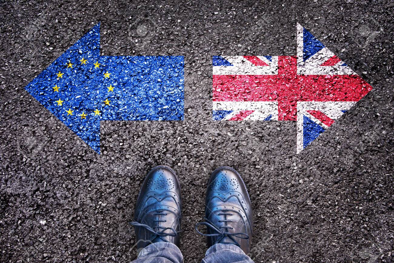 Brexit, flags of the United Kingdom and the European Union on asphalt road with legs - 131101612