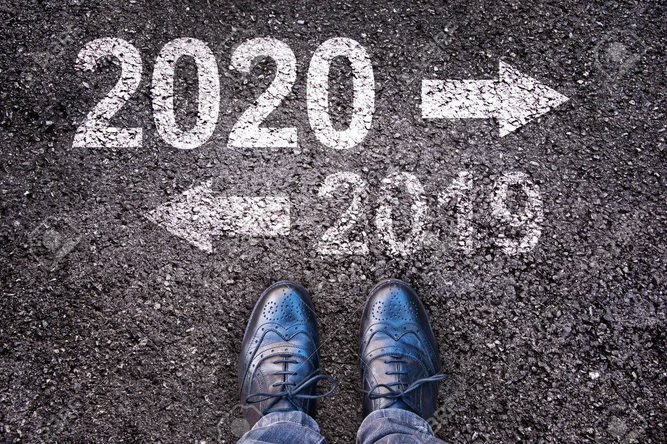 2020 and 2019 with direction arrows written on an asphalt road background with legs - 131101687