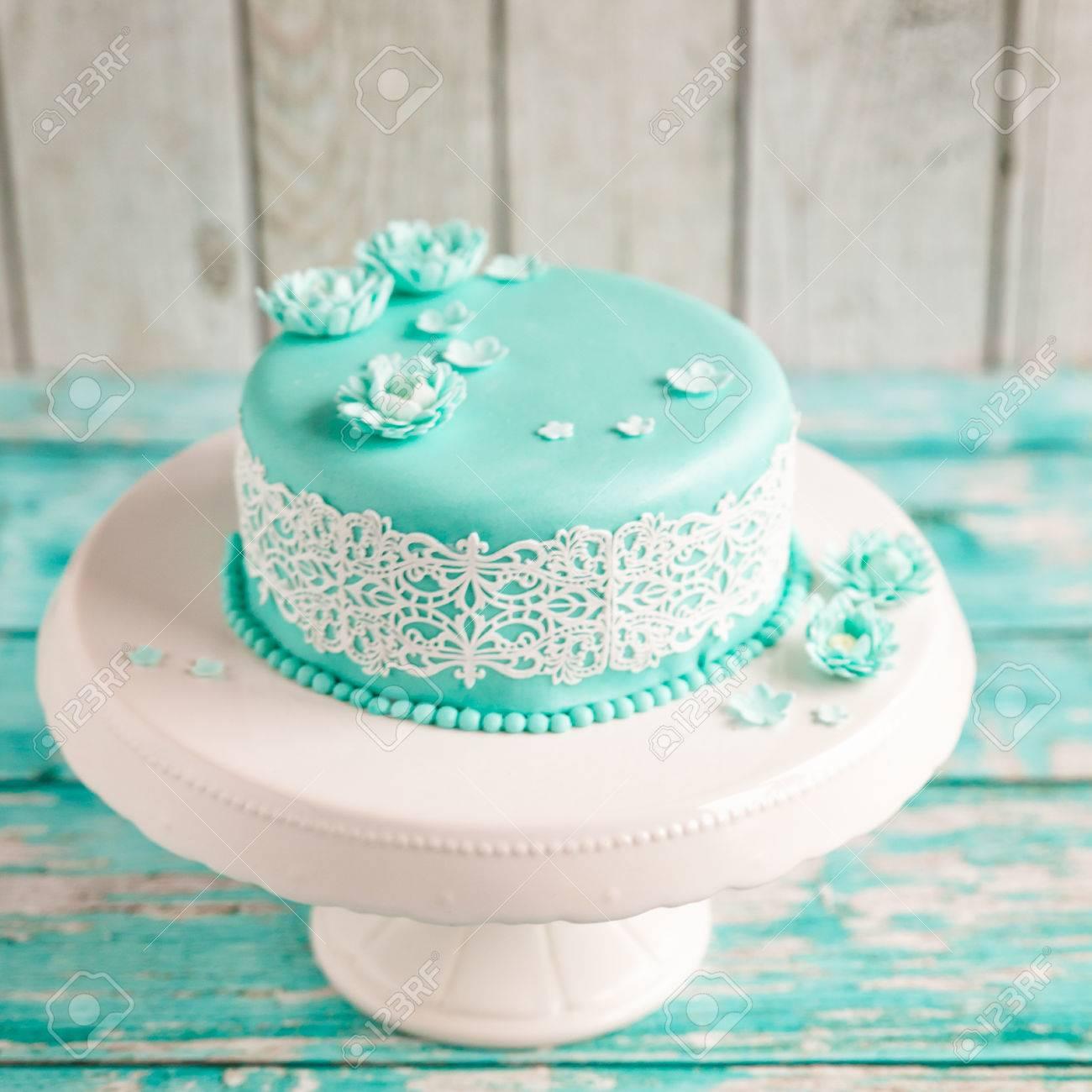 Gâteau De Mariage Avec Mastic Turquoise Et Glaçage En Dentelle Blanche Décoré De Fleurs De Mastic Sur élégant Stand Blanc Sur Fond De Bois