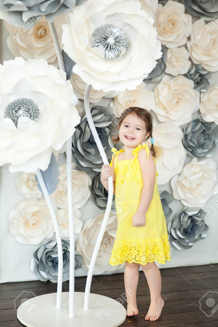 Cute Little Girl With Big Paper Flowers In A Light Spring Studio