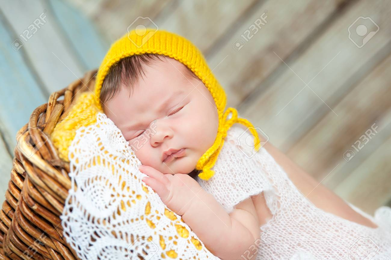 b67185c0d2fb Cute newborn baby girl in a white knit romper and yellow hat..