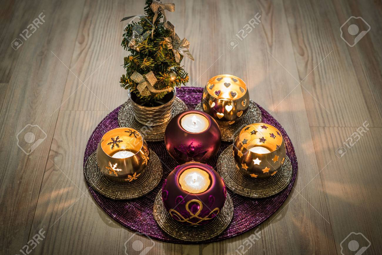 purple and silver christmas candleholders and a small christmas tree on a purple decoration pad with