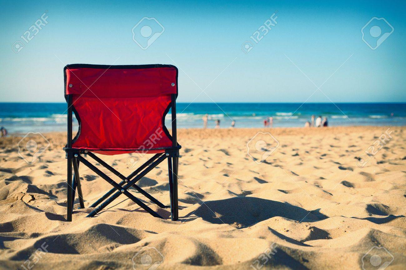 Red chair photography - Red Chair On The Beach With Blurred People In Background Cross Procesing Effects Stock