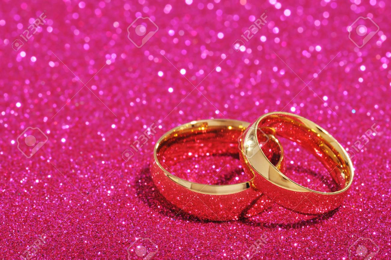 Two Golden Rings On Pink Glitter Background Stock Photo, Picture And ...