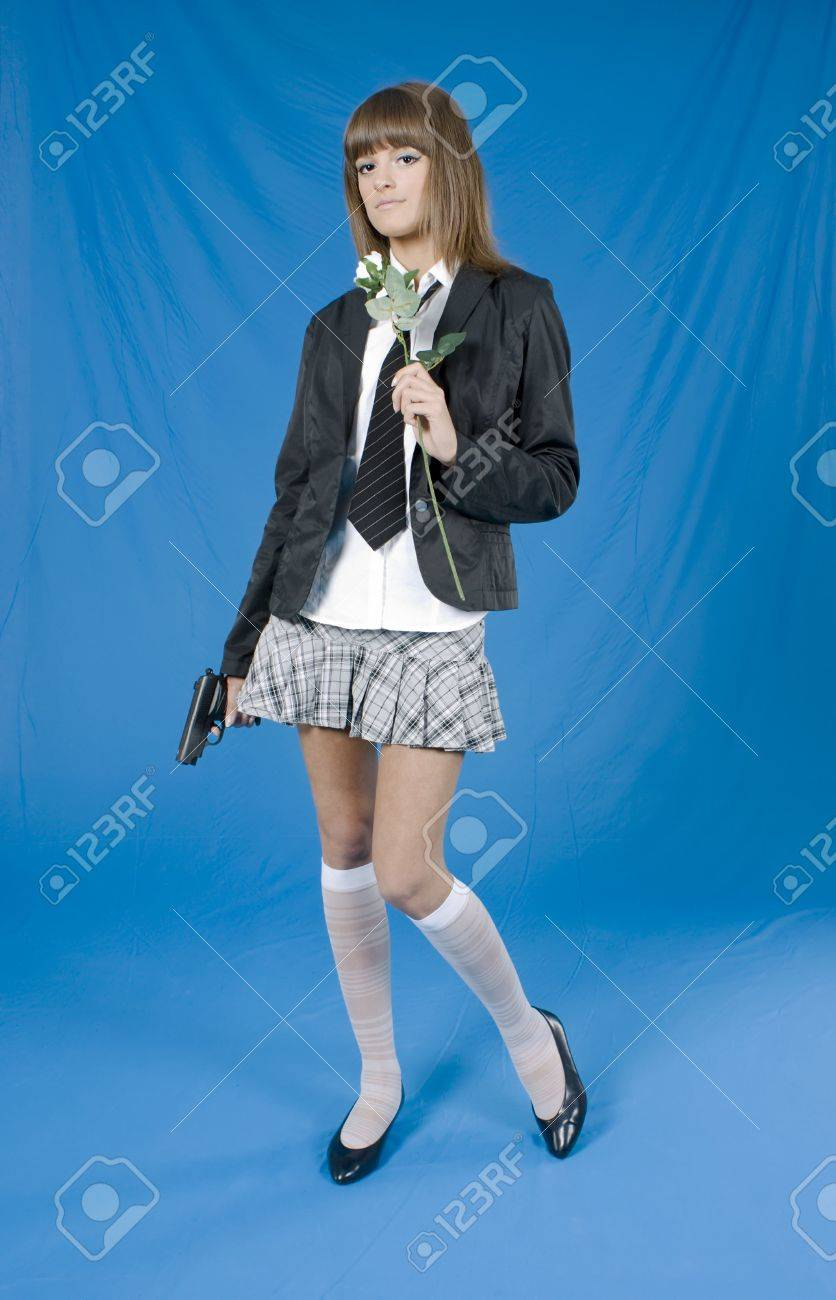 Beautiful young girl with pistol and flower in a hands on blue background Stock Photo - 6249457