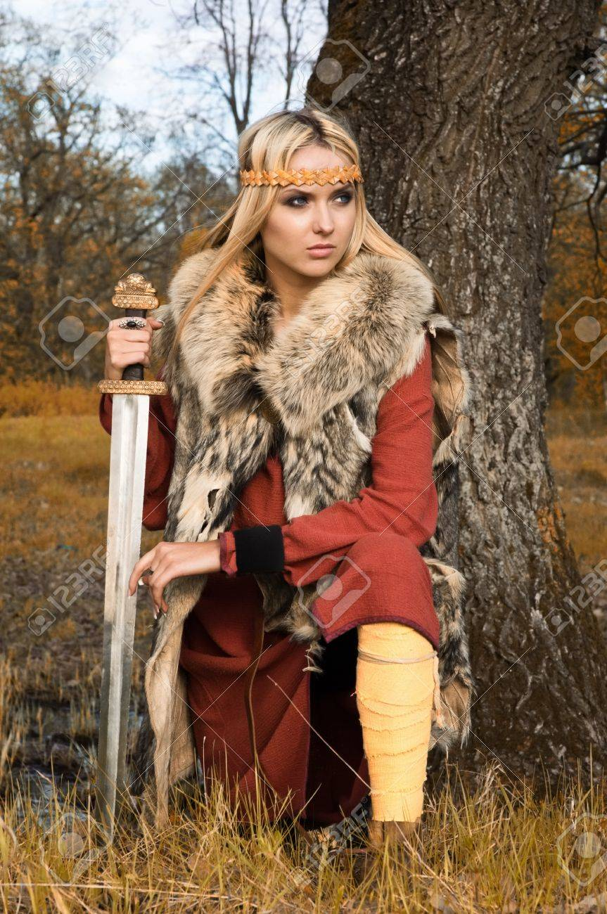 Portrait of the blonde girl in the Scandinavian suit with sword Stock Photo - 9780900