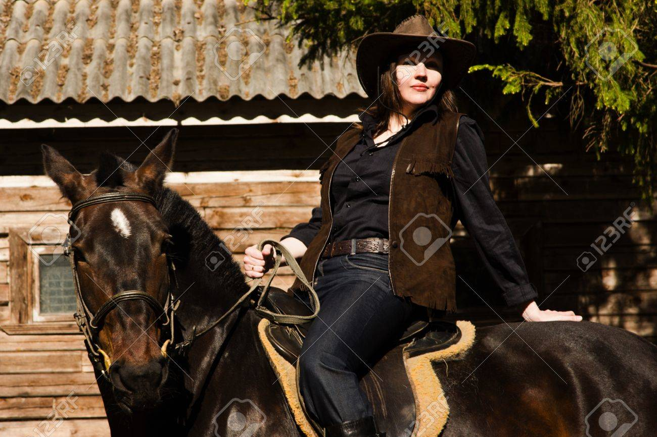 Happy cowgirl in hat on brown horse Stock Photo - 9780617