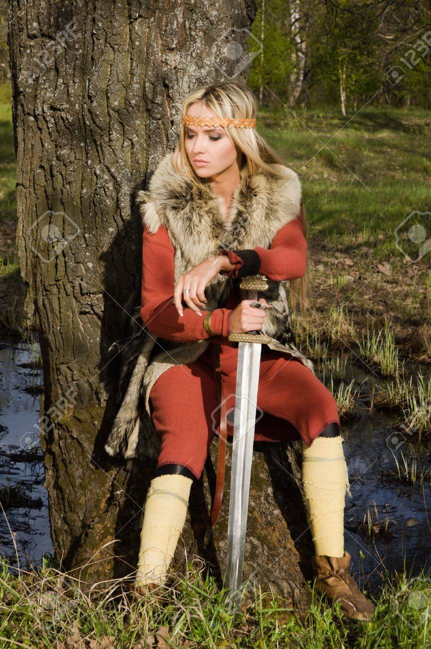 Portrait of the blonde girl in the Scandinavian suit with sword Stock Photo - 9780945
