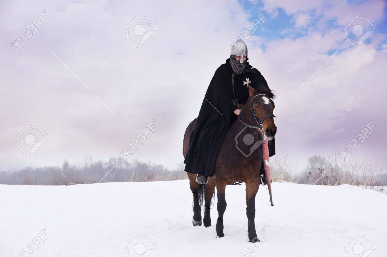 Medieval knight of St. John (Hospitallers) on a bay horses Stock Photo - 13441017