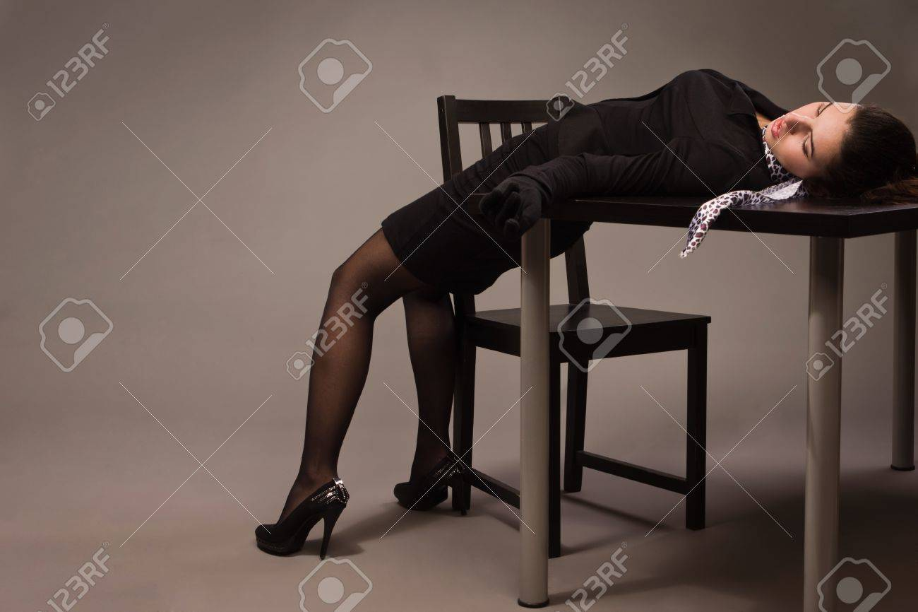 Detective scene imitation. Woman in a black suit lying on a table Stock Photo - 16383147