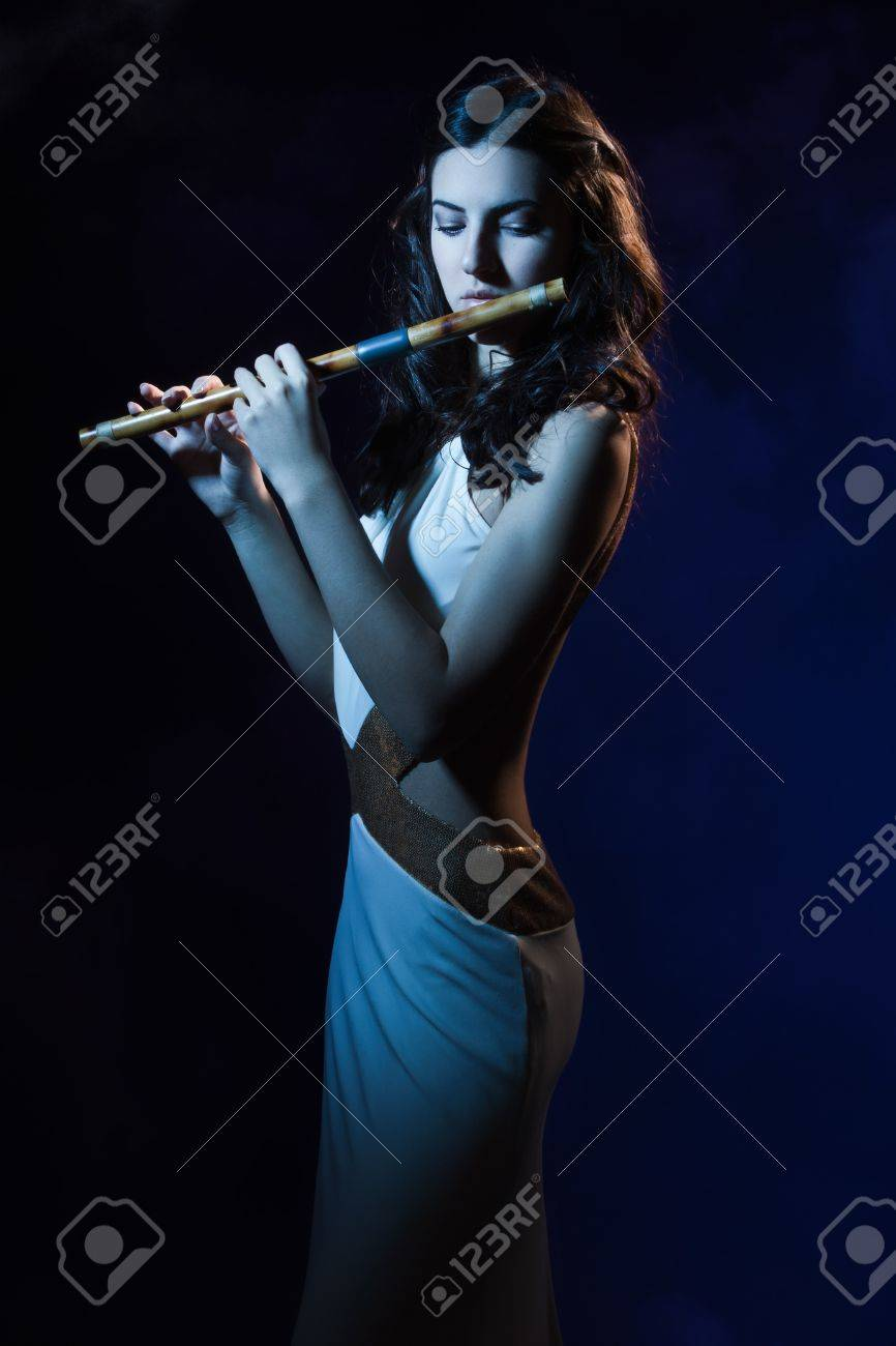 Sensuality beauty brunette plays a wooden flute Stock Photo - 16382914