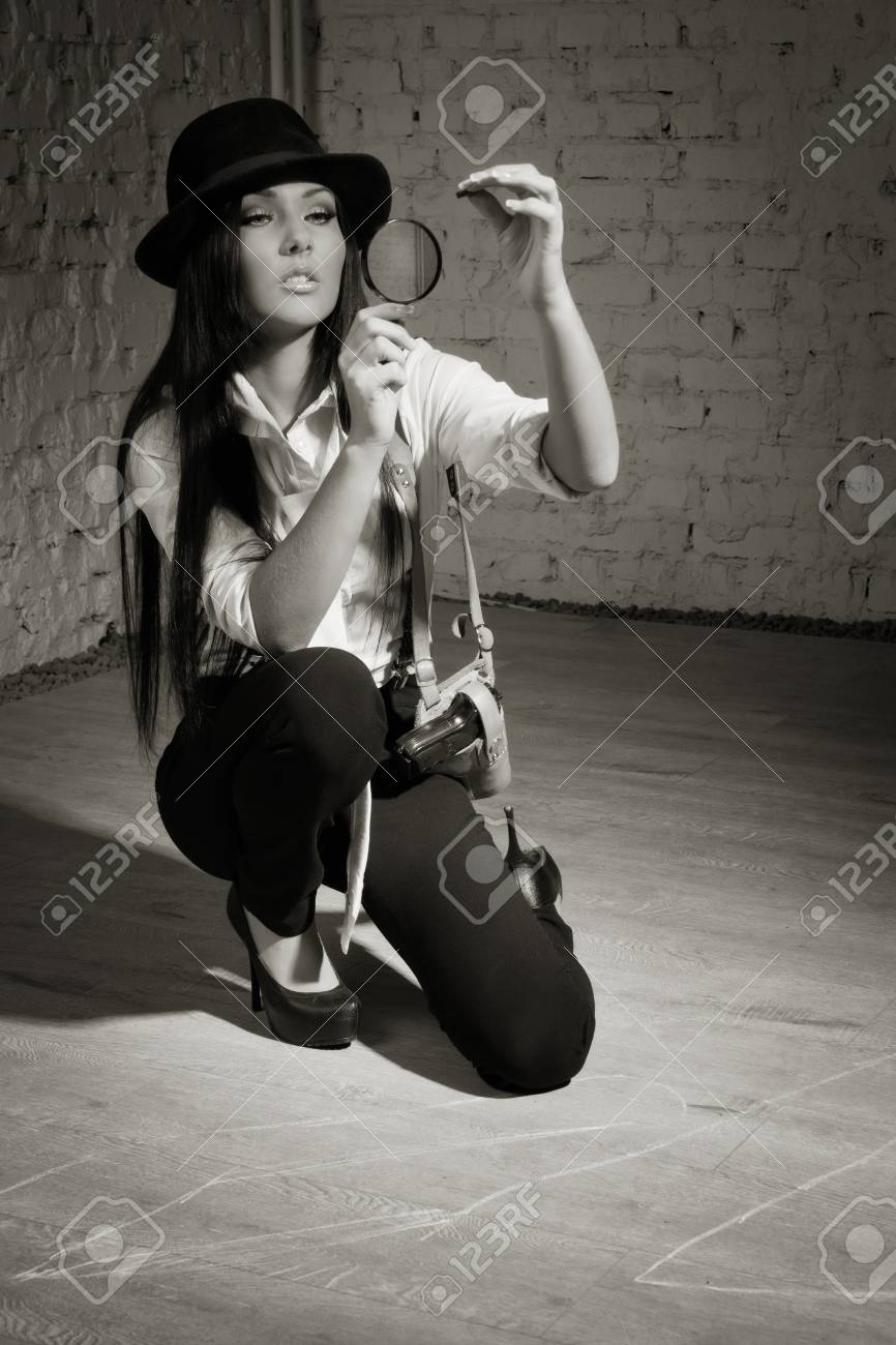 Retro detective girl sees the evidence in the magnifier Stock Photo - 17457930