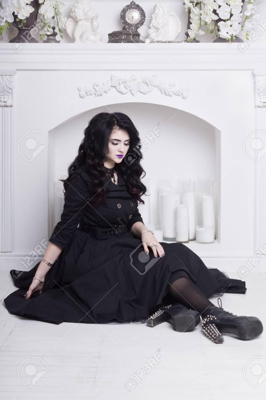 a76a7786126 Sensual gothic woman in a long gorgeous black dress at white..