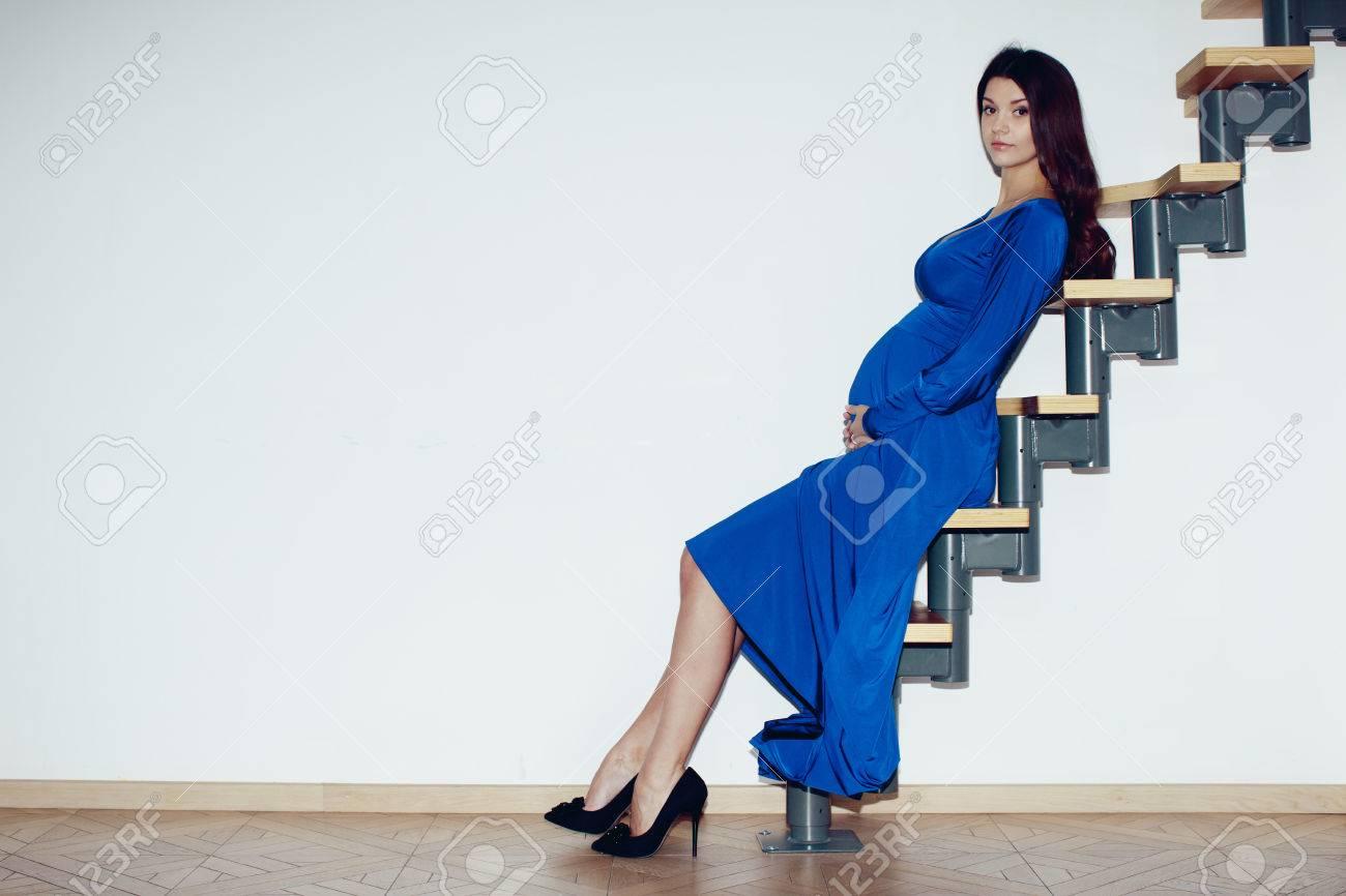 schöne schwangere mädchen, brünett, große brüste, die hände auf bauch,  blaues kleid, auf einer leiter gegen eine weiße wand im inneren sitzen