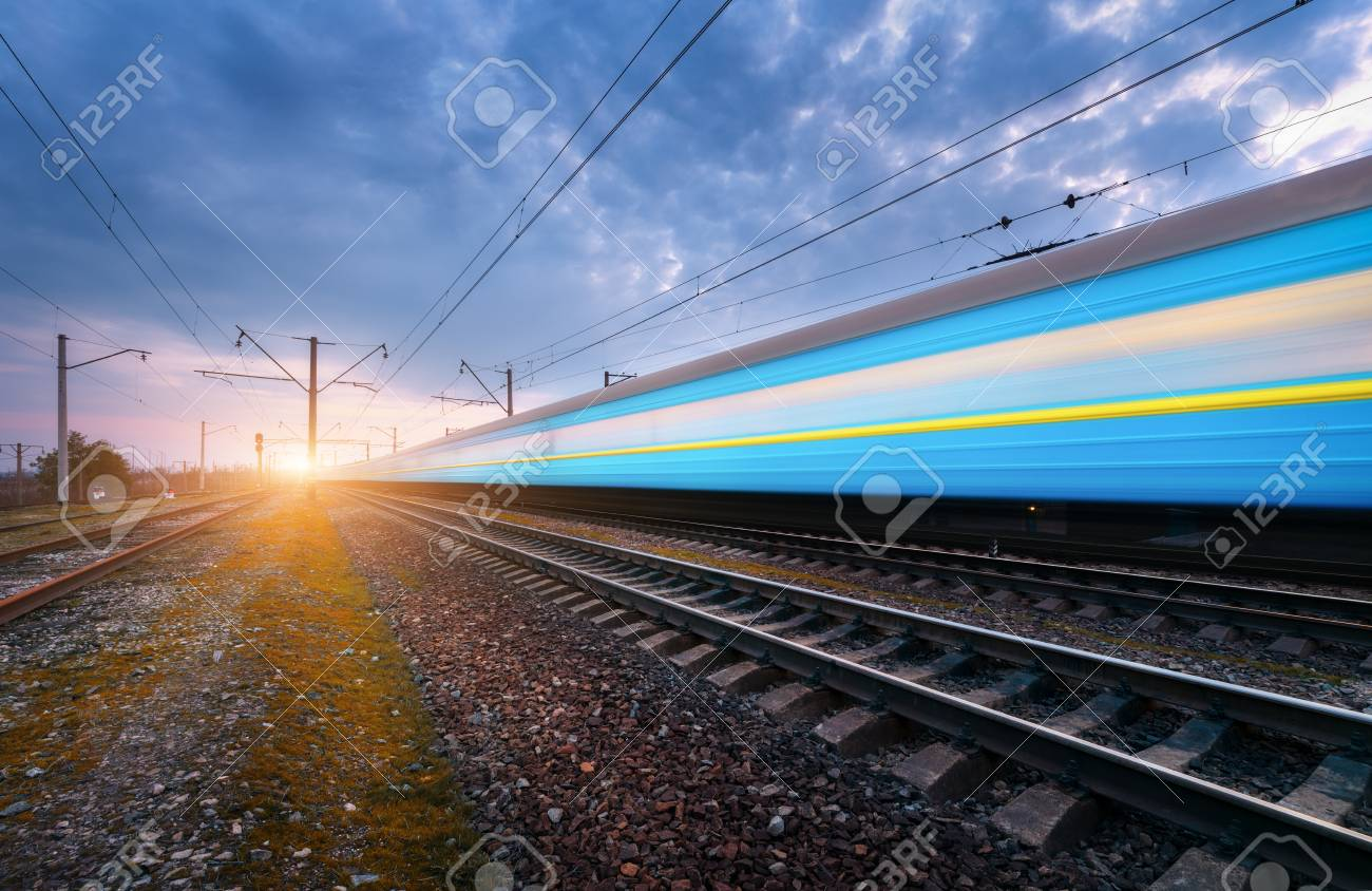 High speed blue passenger train in motion on railroad track at