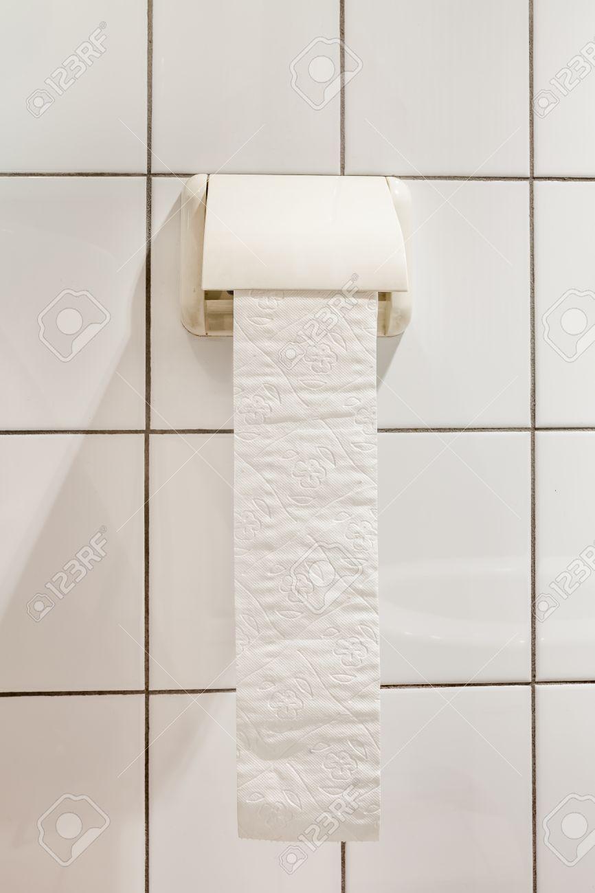 Papier hygiénique accroché au mur. Le papier de toilette sur les carreaux  blancs