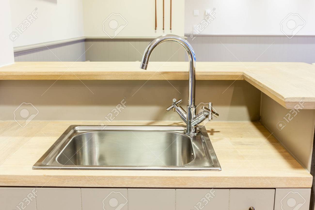 in the kitchen there is a sink built into the wood sheet - 39552263