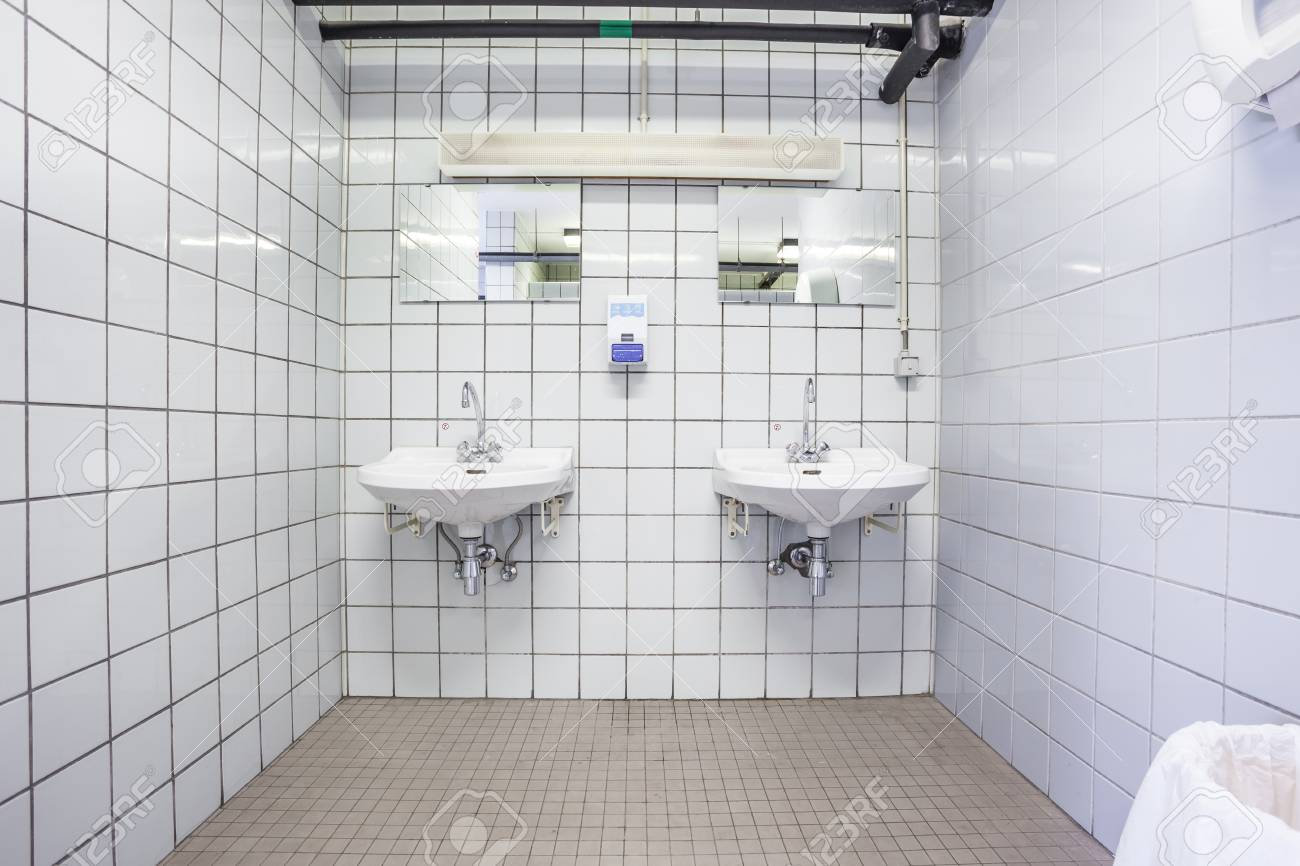 In An Public Restroom Hangs On An Wall Two White Sink Stock Photo ...