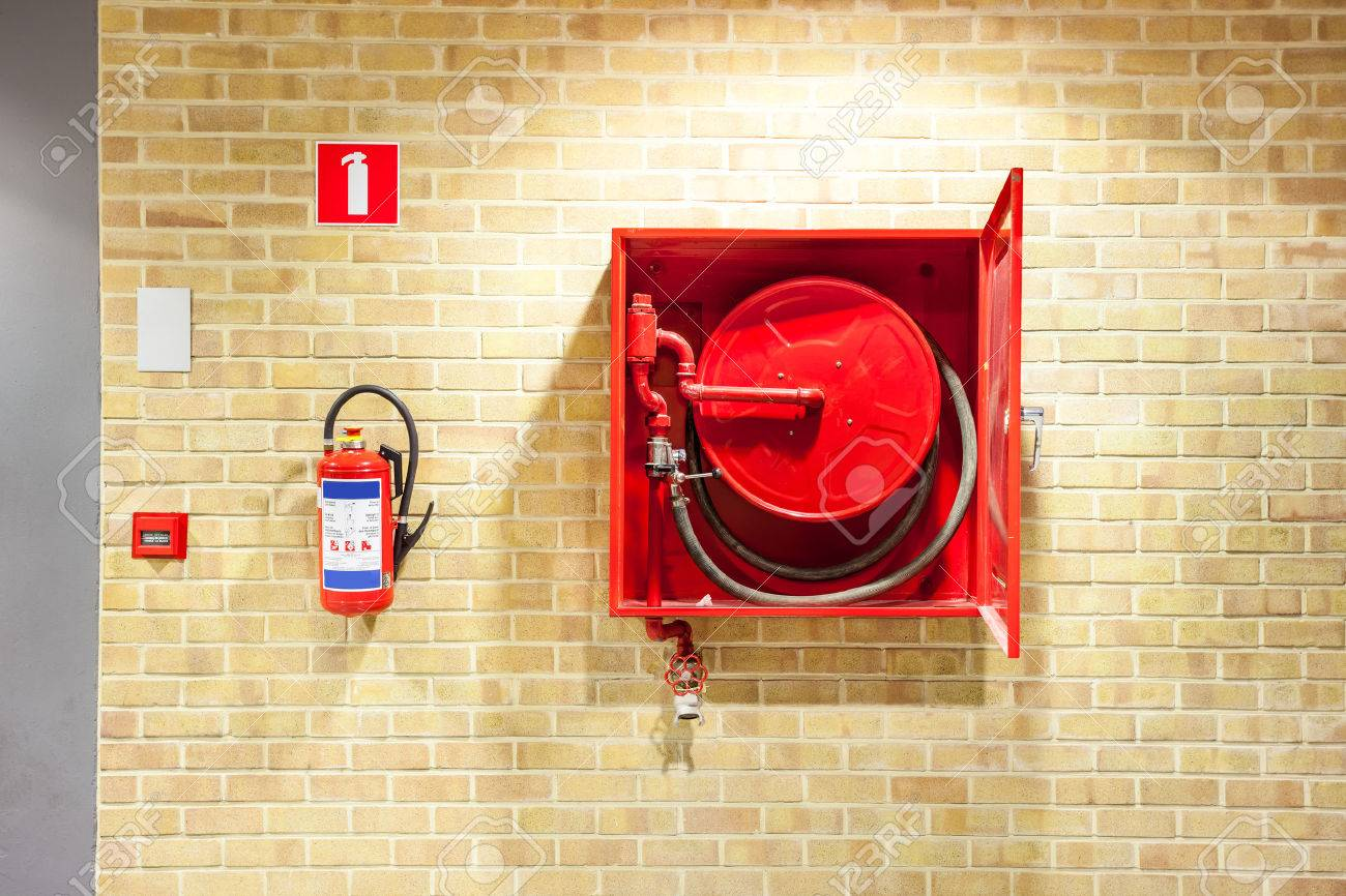 an fire hose hanging on the wall in an staircase - 64874549