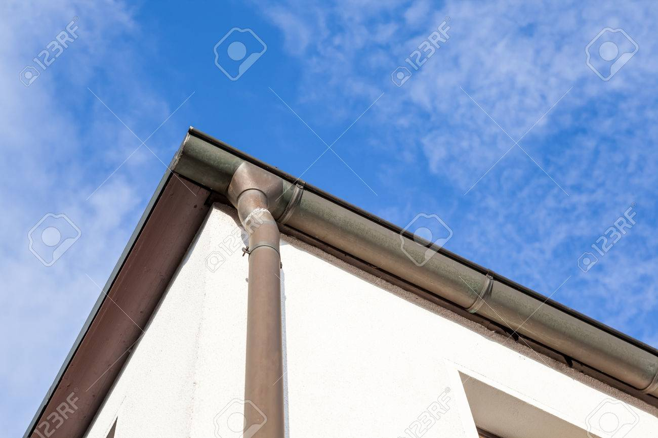 an rain drain pipe from the roof whit blue sky and clouds - 85118106