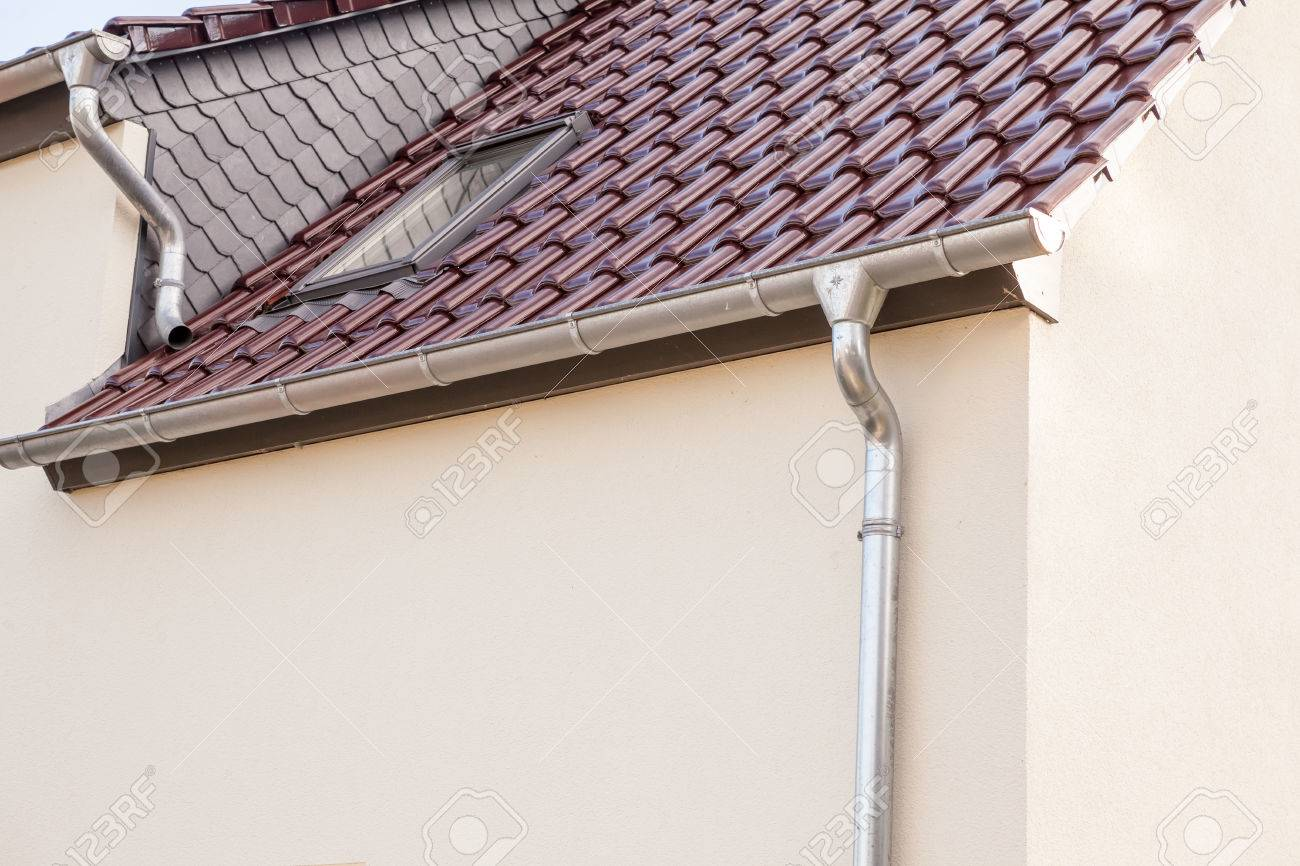 an rain drain pipe from the roof whit blue sky and clouds - 85118253