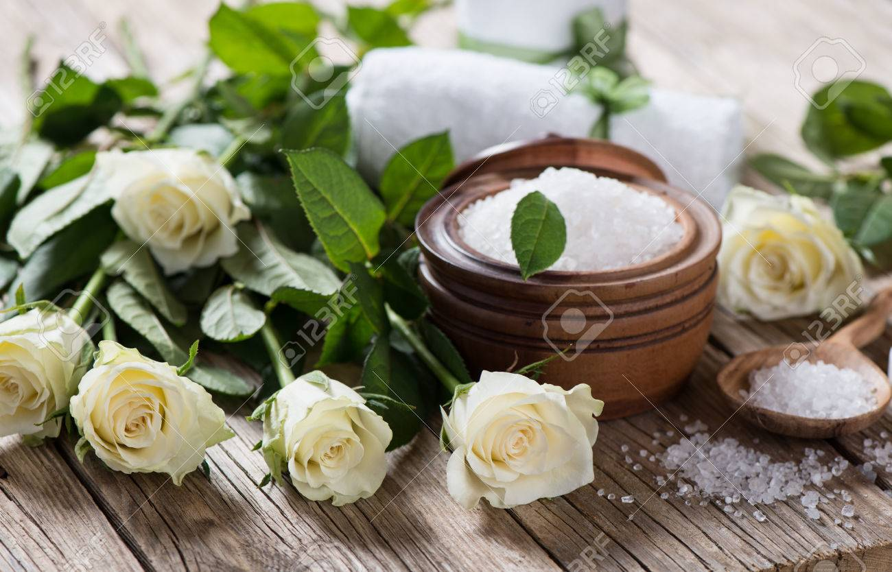 archivio fotografico composizione spa su tavola di legno con rose bianche e bagno di sale