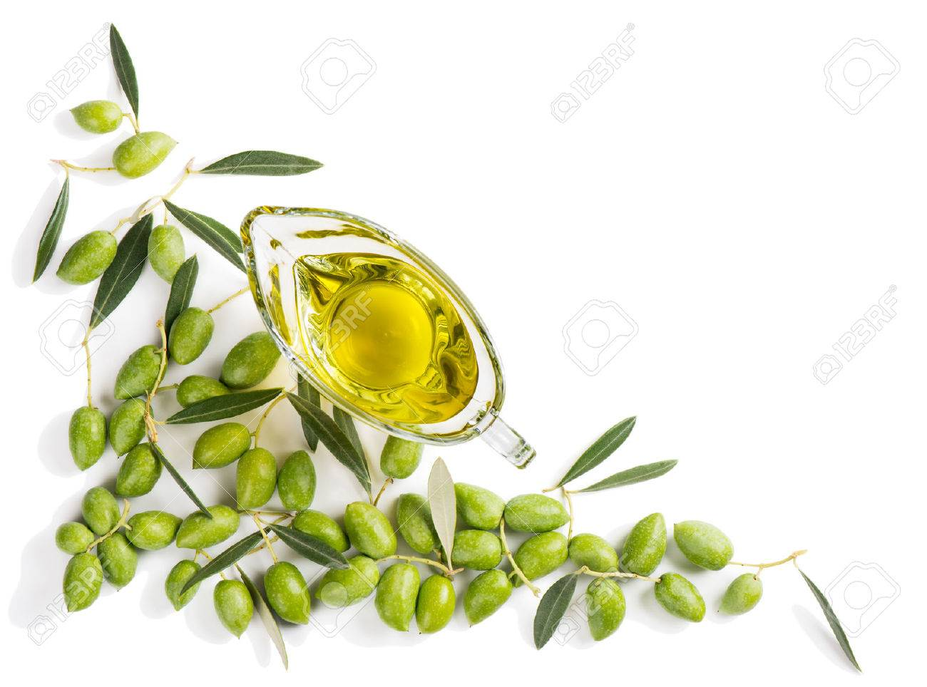 Top view of angular frame of green fresh olives with leaves and olive oil in a glass sauce boat isolated on white background. - 62178739
