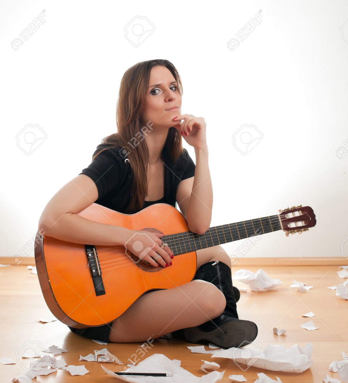 young woman with guitar sitting on floor and writes. woman writes a song Stock Photo - 23461314