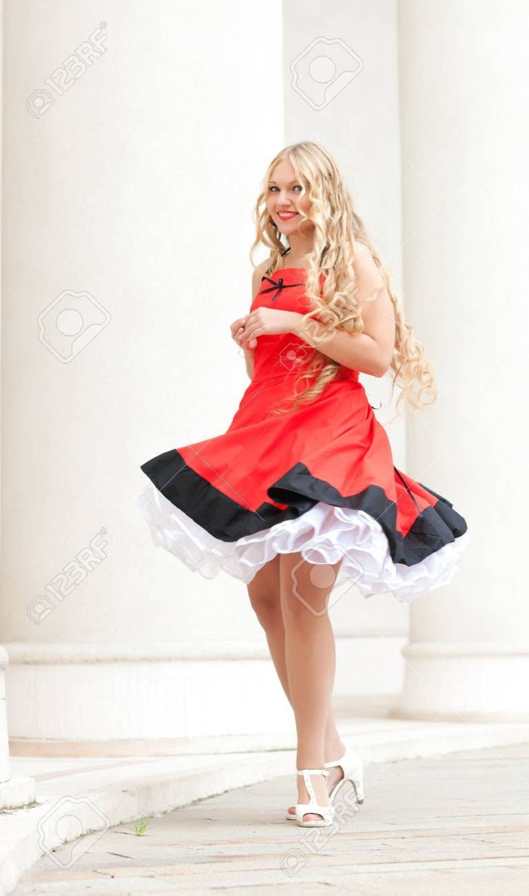 623cbe917 beautiful young woman in old-fashioned dress 50s. wind lifts her dress on a