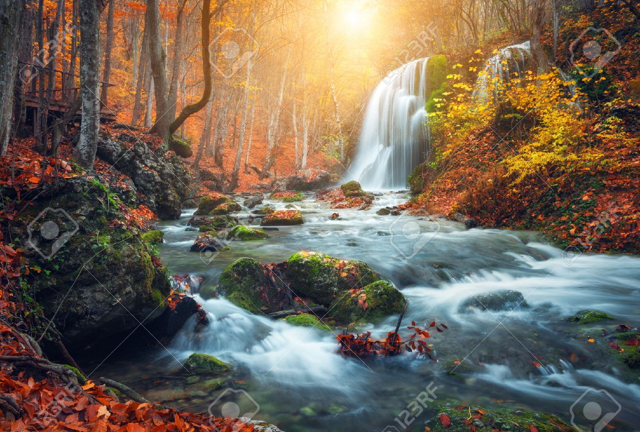 Beautiful waterfall at mountain river in colorful autumn forest beautiful waterfall at mountain river in colorful autumn forest with red and orange leaves at sunset altavistaventures Gallery