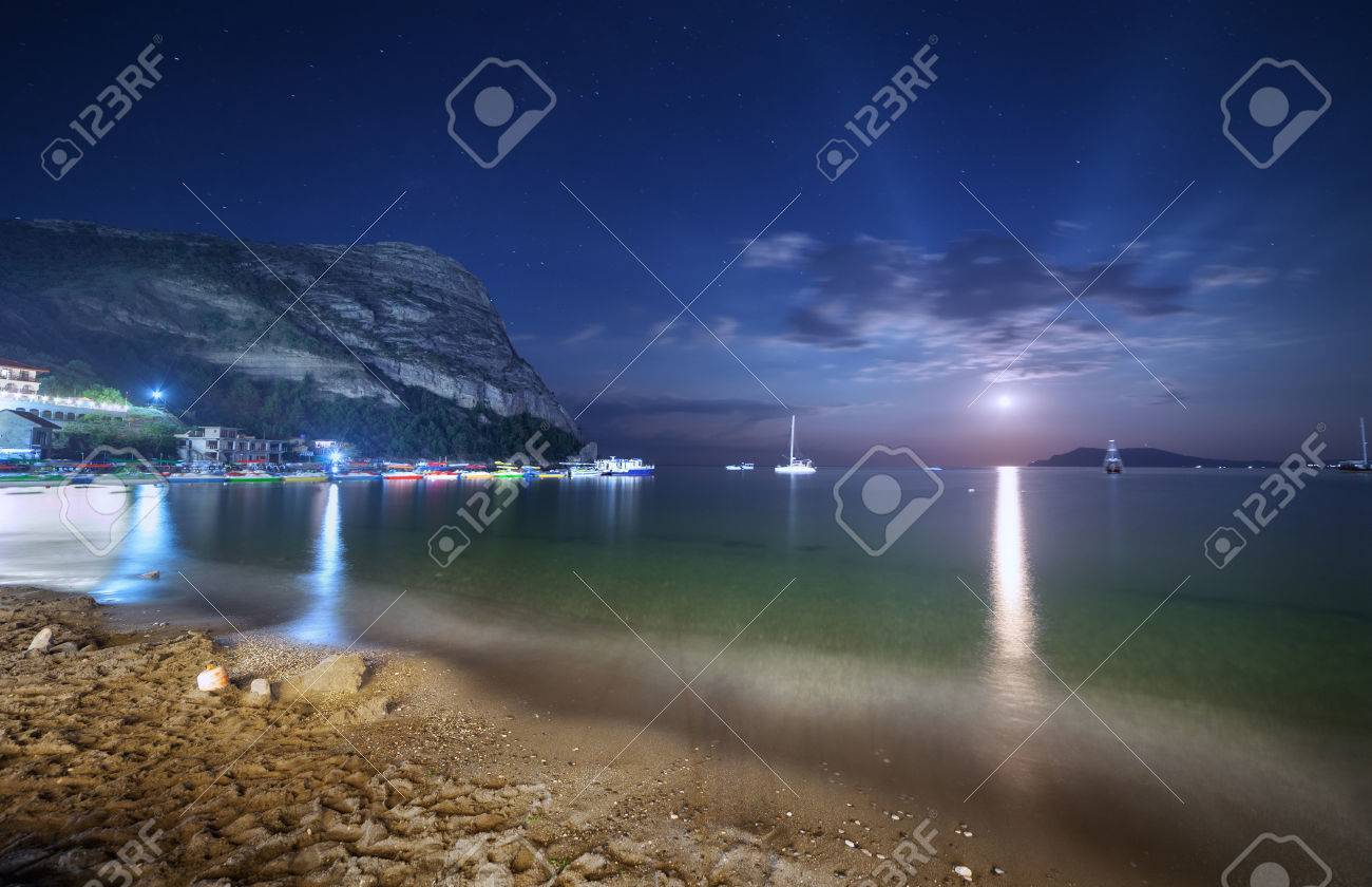 Beautiful Night Landscape At The Seashore With Yellow Sand Full Moon Mountains And Lunar