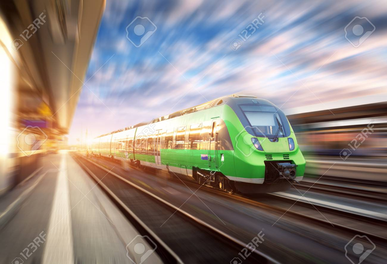 High speed train in motion at the railway station at sunset in Europe. Beautiful green modern train on the railway platform with motion blur effect. Industrial scene with passenger train on railroad - 81440795