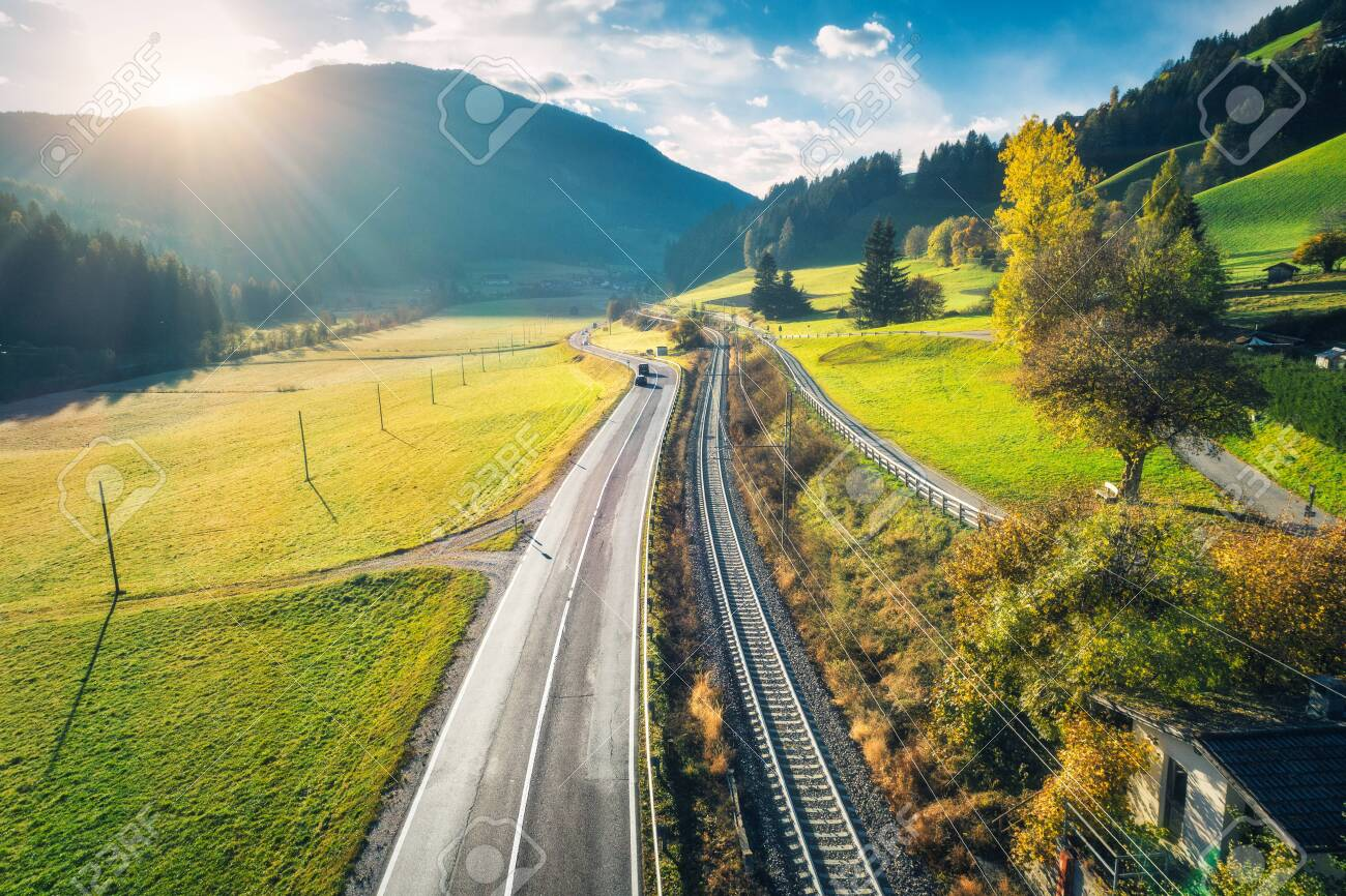 a80157367c495 ... at sunset in spring in Dolomites, Italy. Top view of asphalt roadway,  railroad, hills with green meadows, blue sky, trees, buildings. Highway and  fields