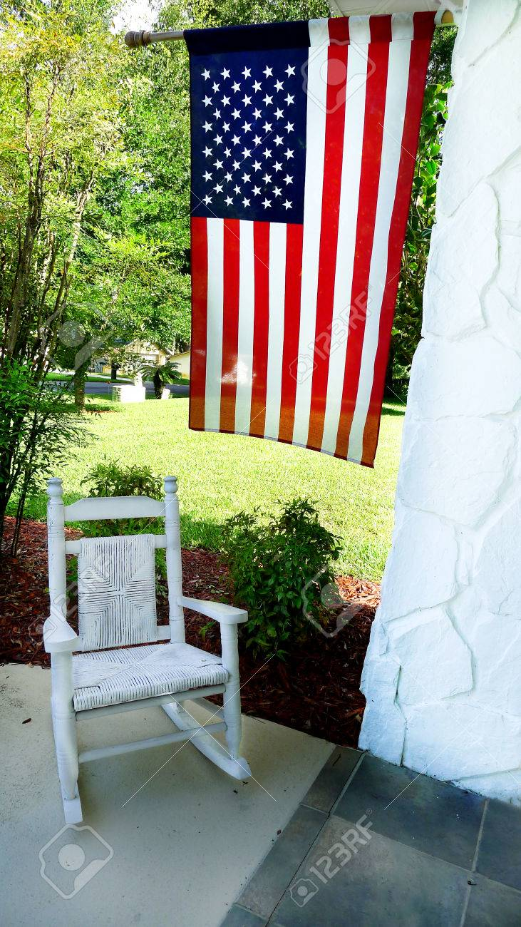 American Flag Overhanging On Porch With Childu0027s Wicker Rocking Chair In  Country Front Yard. Stock