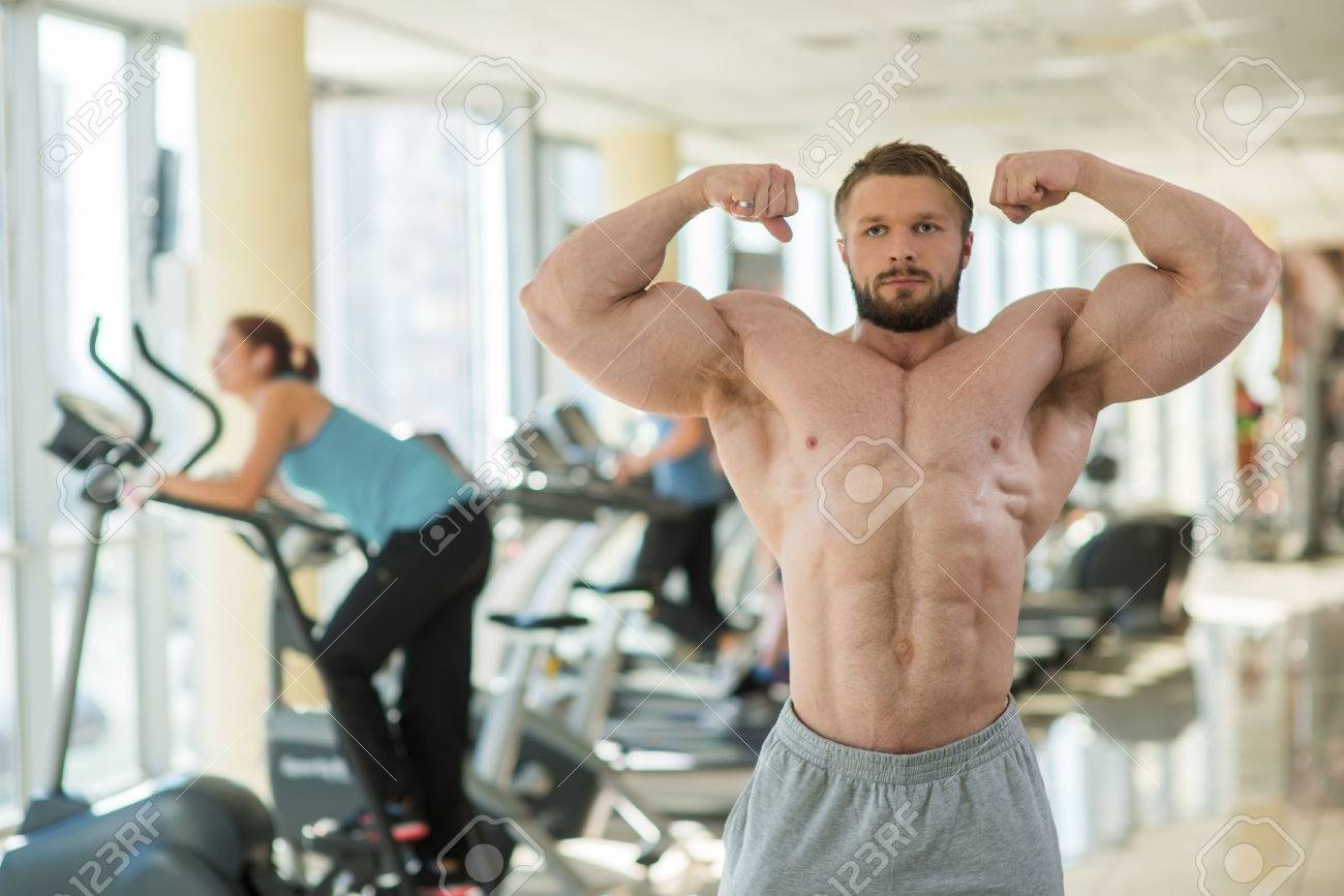 Muskulöser Mann In Fitness-Studio. Sportler Seine Muskeln Zeigt ...