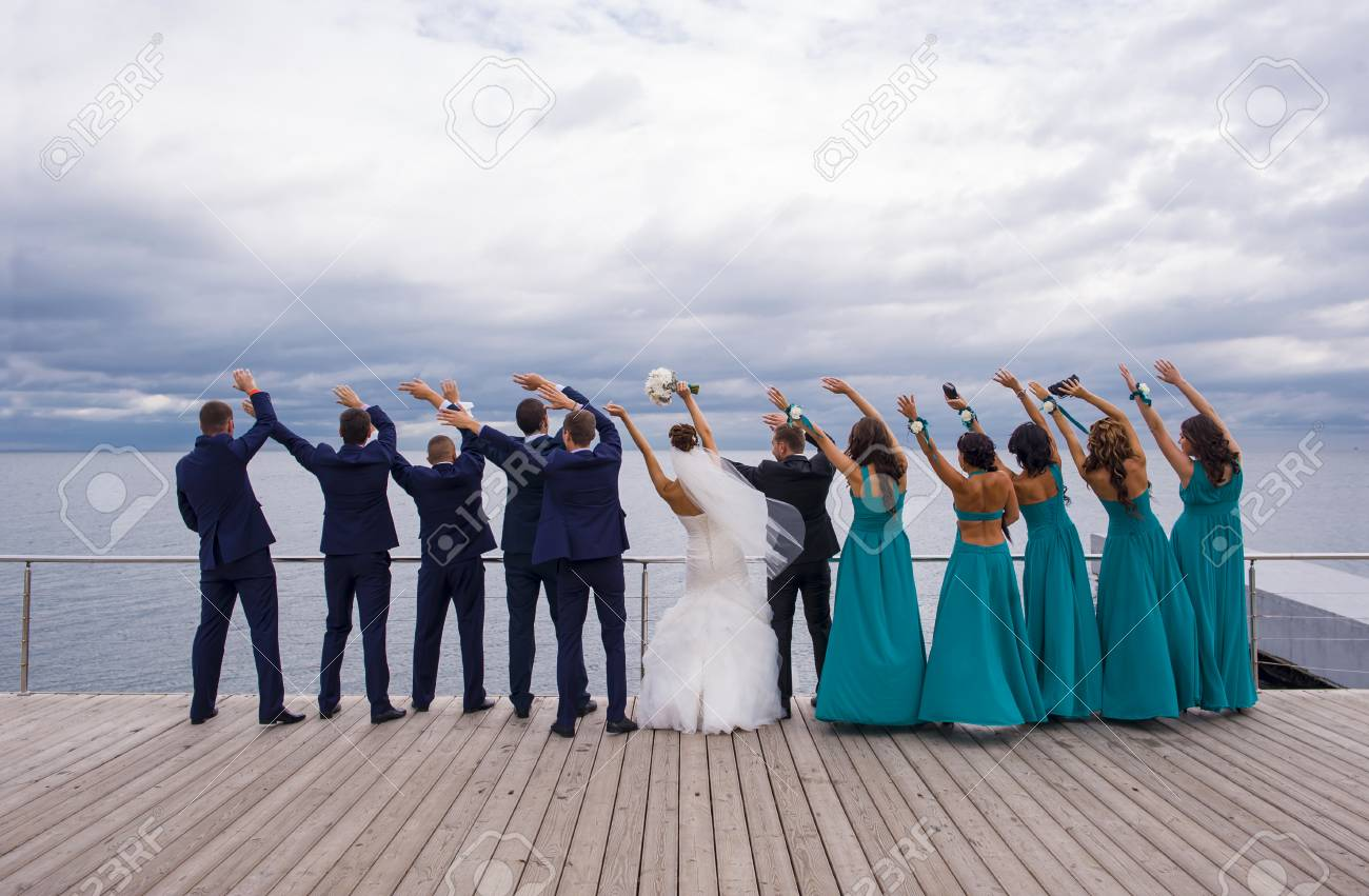 Guests on the wedding celebration are standing on the river quay, holding their hands up and playing the game. - 51166266