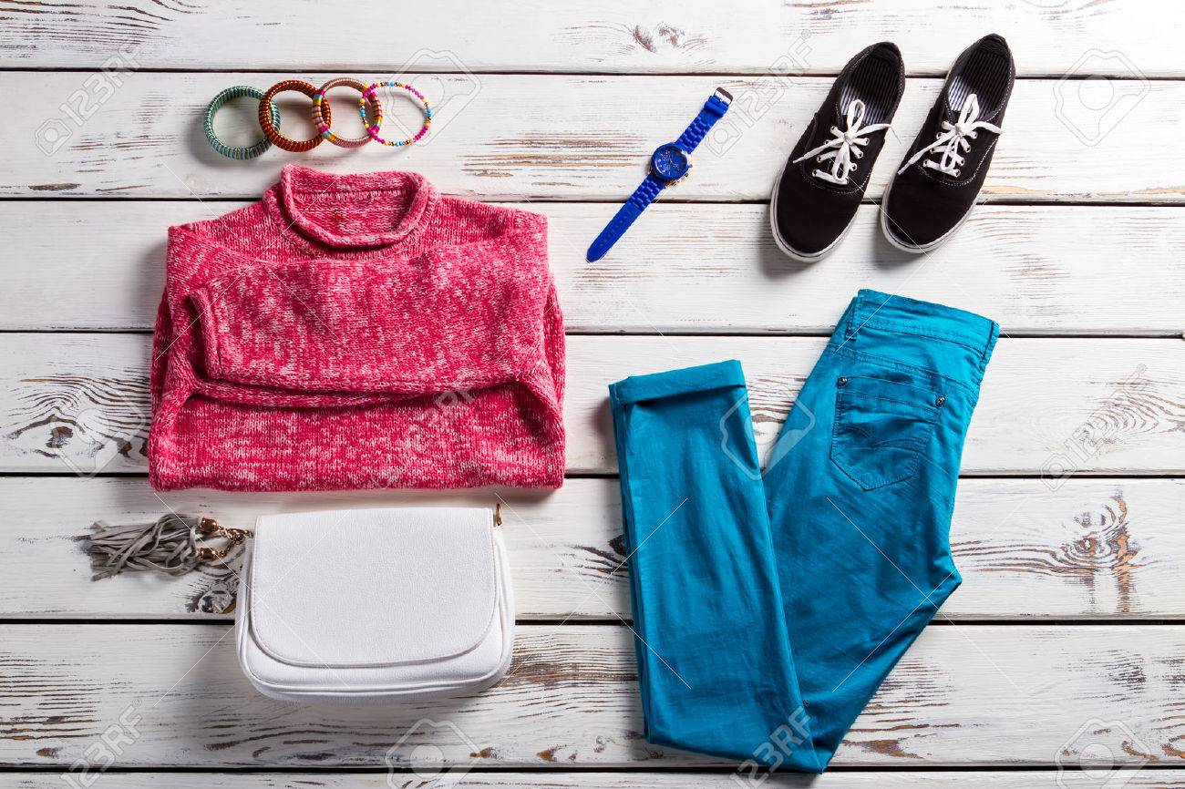 Lady's outfit with pink pullover. Colorful clothes on white shelf. Bright-colored casual clothing. Female clothes and simple shoes. - 55415108