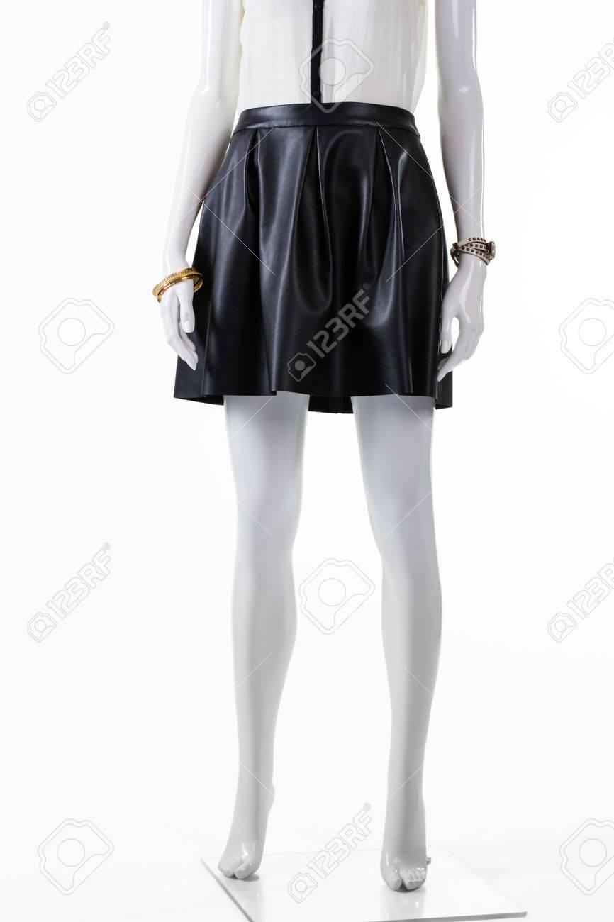 72fd0ddb244a Falda corta de cuero sobre maniquí. Accesorios de falda oscura y muñeca.  Elegante falda con reloj pequeño. Traje de joven para la noche.