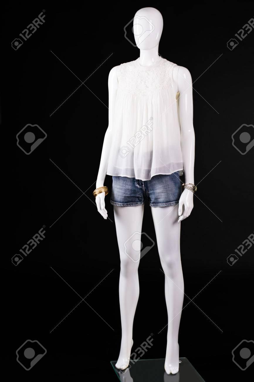 Blanc haut et short en jean. Mannequin femme en haut blanc. tenue d'été sur fond sombre. look élégant de jeune dame.