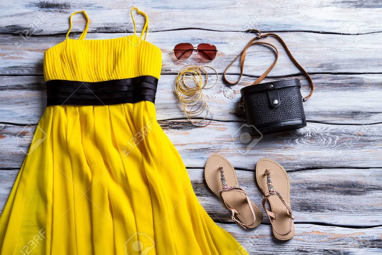 c40b77c88ed Banque d images - Robe jaune et beige sandales. Sandals
