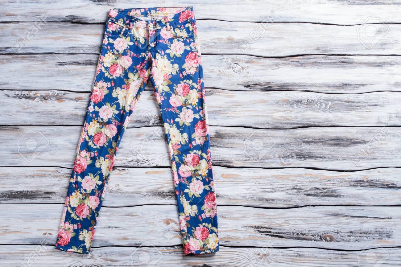 divers styles personnalisé meilleur prix Pantalon bleu avec motif de fleurs. Pantalons femme sur fond en bois.  Nouveauté et style Des vêtements de qualité vendus à prix réduit.