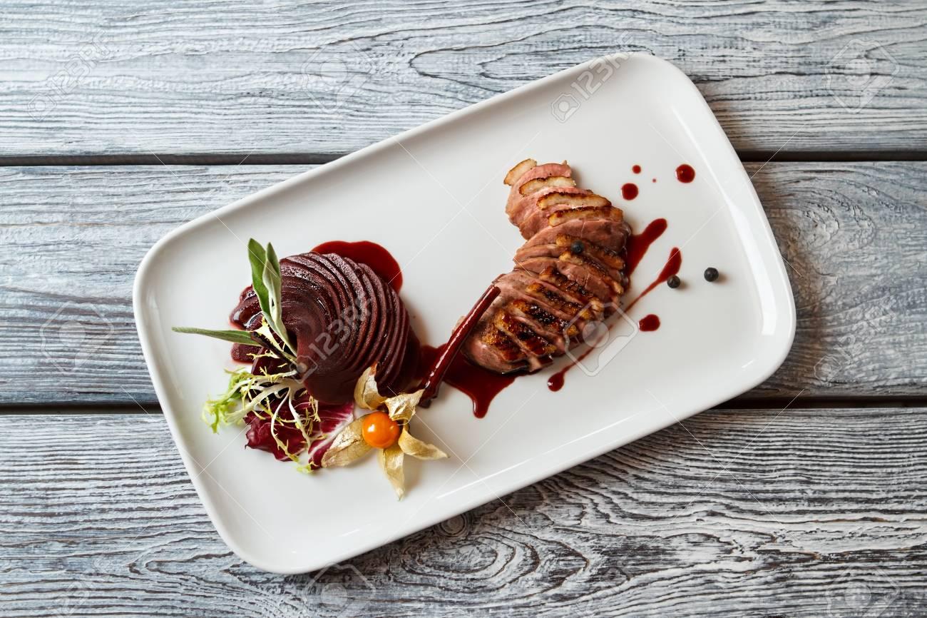 Assiette avec de la viande cuite. Tranches de viande avec décoration.  Magret de canard avec une sauce sucrée. Délicatesse de la cuisine  européenne.